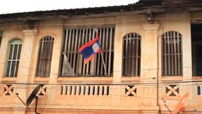 垂悬从一个恶化的共产主义样式家的老挝旗子在Suvannakhet 股票录像
