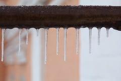 垂悬从一个棕色管子的冰柱 冻结的水和金属表面,冬时概念 选择聚焦浅深度  库存图片