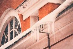 垂悬从一个老房子的屋顶的巨大的冰柱在莫斯科 库存照片