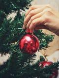 垂悬从一棵装饰的圣诞树的红色中看不中用的物品特写镜头 葡萄酒过滤器作用 免版税库存照片