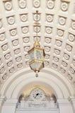 垂悬从在时钟前面的被装饰的天花板的枝形吊灯 免版税库存图片
