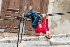 垂悬从在街道的栏杆的孩子 使用在街道的孩子 免版税库存照片