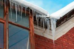 垂悬从壁角屋顶的普通的冰柱在窗口反对一朵蓝天和白色云彩 免版税库存照片