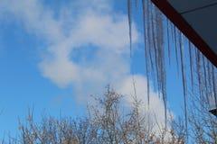 垂悬从大厦的屋顶的冰柱反对蓝天 免版税库存图片
