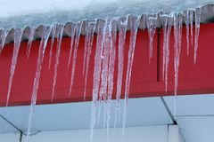 垂悬从大厦的屋顶的冰柱 图库摄影