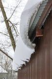 垂悬从屋顶的随风飘飞的雪下来 免版税库存照片