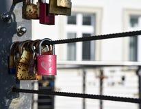 垂悬从桥梁的一把红色锁的一张忧郁的照片代表爱和秘密 免版税库存图片