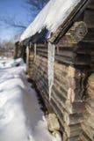 垂悬从老原木小屋和滴下的屋顶的冰柱 免版税库存照片