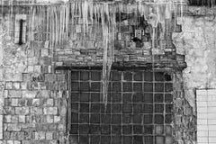 垂悬从老砖瓦房的屋顶的冰柱与老瓦片,创伤尖酸冰,解冻在早期的春天, bl立方体的  免版税库存图片