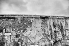 垂悬从老砖瓦房的屋顶的冰柱与老瓦片,创伤尖酸冰,解冻在早期的春天, bl立方体的  免版税库存照片