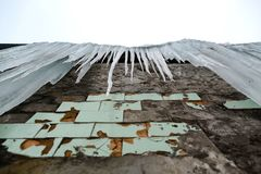 垂悬从老砖瓦房的屋顶的冰柱与老瓦片,创伤尖酸冰,解冻在早期的春天, lo立方体的  免版税库存图片