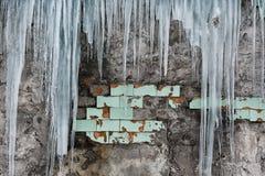 垂悬从老砖瓦房的屋顶的冰柱与老瓦片,创伤尖酸冰,解冻在早期的春天, se立方体的  免版税库存照片