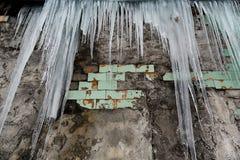 垂悬从老砖瓦房的屋顶的冰柱与老瓦片,创伤尖酸冰,解冻在早期的春天, se立方体的  库存照片