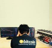 垂悬他的在一张碰撞的bitcoin股票图前面的一个人头 免版税库存图片