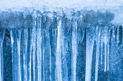垂悬反对墙壁背景的冰柱  免版税图库摄影