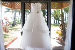 垂悬反对窗口的新娘婚装 免版税图库摄影