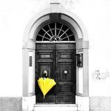 垂悬在一个传统意大利门道入口的外部的一把黄色伞在托斯卡纳 图库摄影