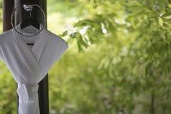 垂悬在一个卫生间设计的一个挂衣架的白色浴巾在o 库存图片