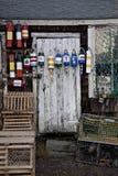垂悬在一个土气棚子的明亮,五颜六色的bouys 库存图片