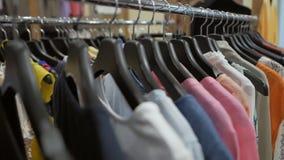 垂悬在一个挂衣架的明亮的夏天衣裳在商店 影视素材