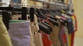 垂悬在一个挂衣架的明亮的夏天衣裳在商店 股票录像