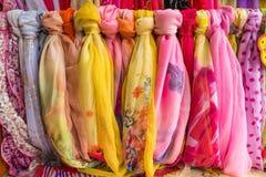 垂悬在一个木挂衣架的多彩多姿的围巾 免版税图库摄影