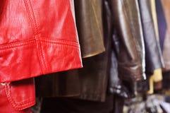 垂悬在一个机架的皮革衣裳在跳蚤市场上 免版税库存图片