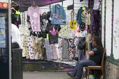 垂悬在一个机架的衣裳在跳蚤市场上 库存照片