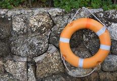 垂悬在一个石墙上的Lifebuoy 免版税图库摄影