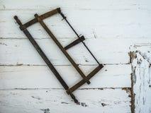 垂悬在一个老房子的墙壁上的锯 免版税库存照片