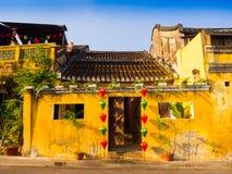 垂悬在一个老黄色房子外面的绿色和红色灯笼在会安市古镇,联合国科教文组织世界遗产 会安市是 库存照片