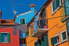 垂悬在一个胡同的五颜六色的露台的房子、阳台和衣裳看法在Burano 免版税库存图片