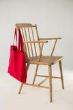 垂悬在一把木椅子的红色袋子 库存图片