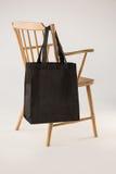 垂悬在一把木椅子的黑袋子 免版税库存照片