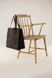 垂悬在一把木椅子的黑袋子 图库摄影