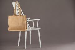 垂悬在一把白色椅子的米黄织品袋子 免版税库存图片