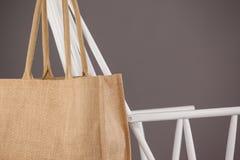 垂悬在一把白色椅子的米黄织品袋子 库存图片