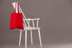 垂悬在一把白色椅子的红色袋子 免版税库存照片