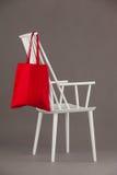垂悬在一把白色椅子的红色袋子 免版税库存图片