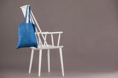 垂悬在一把白色椅子的蓝色袋子 免版税图库摄影