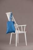 垂悬在一把白色椅子的蓝色袋子 库存照片
