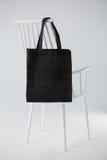 垂悬在一把白色椅子的黑袋子 库存图片
