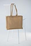垂悬在一把白色椅子的黄麻袋子 免版税库存照片