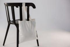 垂悬在一把黑椅子的白色袋子 免版税图库摄影