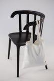 垂悬在一把黑椅子的白色袋子 库存照片