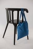 垂悬在一把黑椅子的蓝色袋子 免版税库存图片