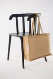 垂悬在一把黑椅子的黄麻袋子 库存照片