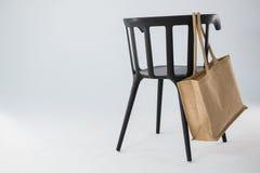 垂悬在一把黑椅子的黄麻袋子 免版税库存照片
