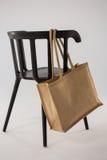 垂悬在一把黑椅子的黄麻袋子 库存图片