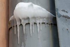 垂悬在一支冻水管的冰柱在屋顶 秋天 背景蓝色雪花白色冬天 软绵绵地集中 图库摄影
